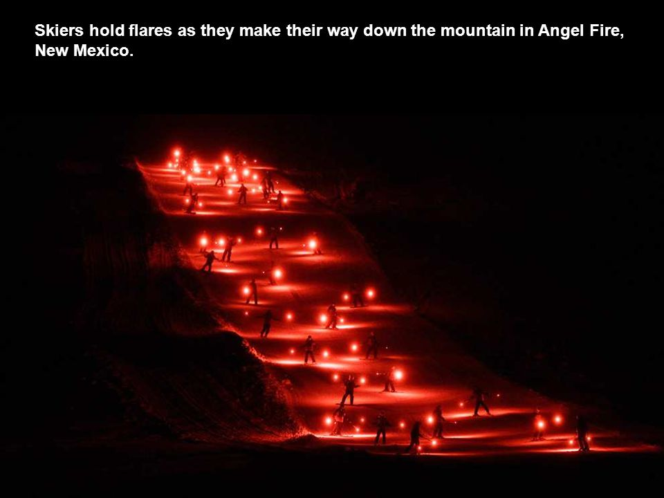 Skiers hold flares as they make their way down the mountain in Angel Fire, New Mexico.