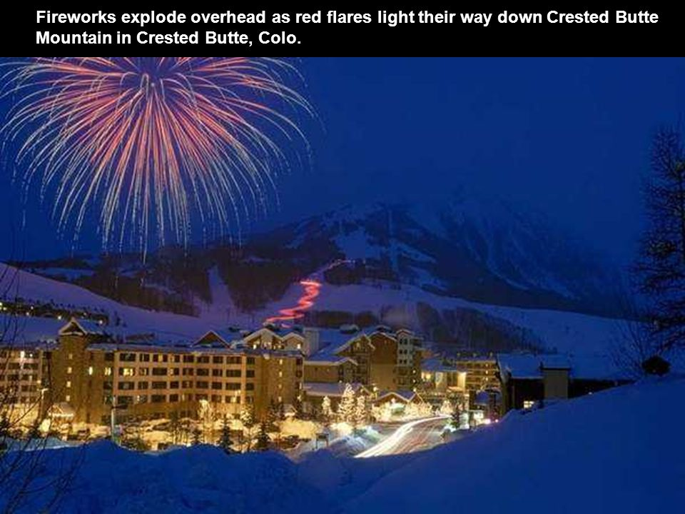 Fireworks explode overhead as red flares light their way down Crested Butte Mountain in Crested Butte, Colo.