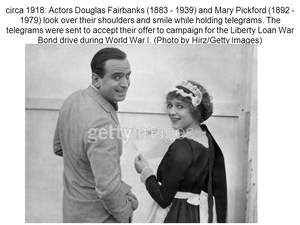 circa 1918: Actors Douglas Fairbanks (1883 - 1939) and Mary Pickford (1892 - 1979) look over their shoulders and smile while holding telegrams.