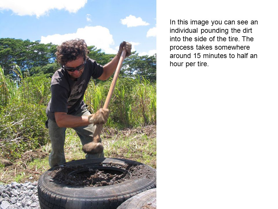 In this image you can see an individual pounding the dirt into the side of the tire.