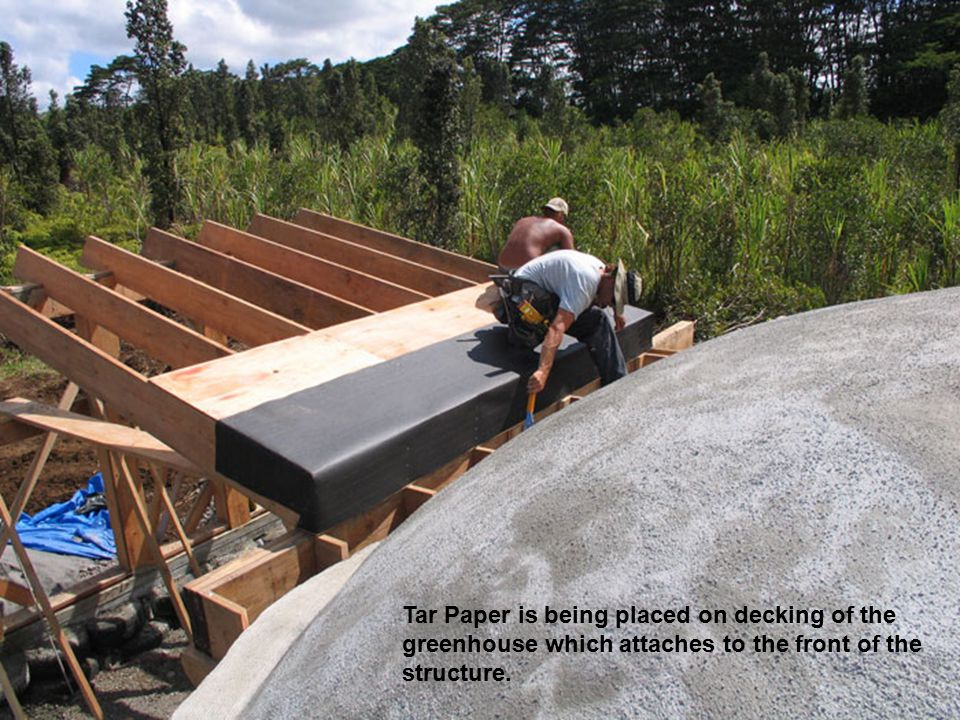 Tar Paper is being placed on decking of the greenhouse which attaches to the front of the structure.