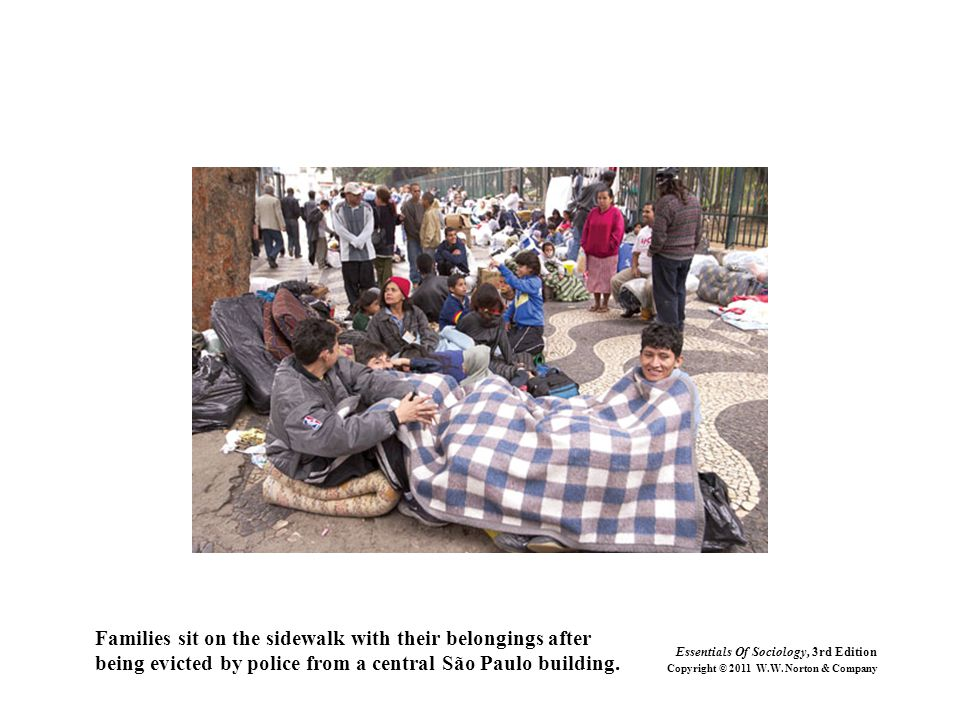 Families sit on the sidewalk with their belongings after