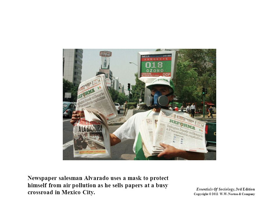 Newspaper salesman Alvarado uses a mask to protect