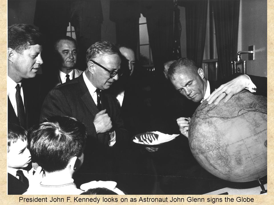 President John F. Kennedy looks on as Astronaut John Glenn signs the Globe