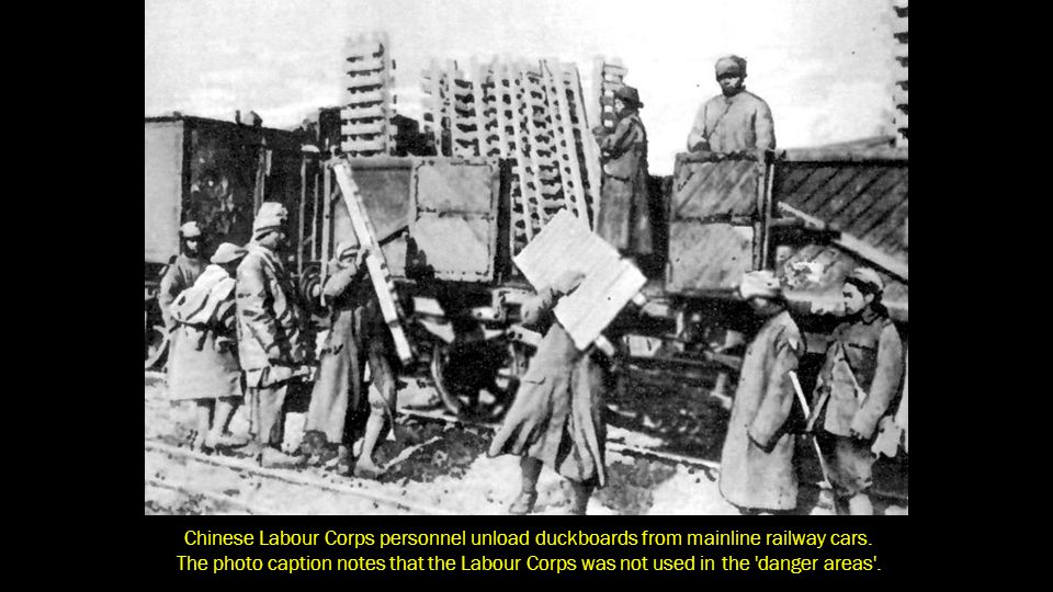Chinese Labour Corps personnel unload duckboards from mainline railway cars.