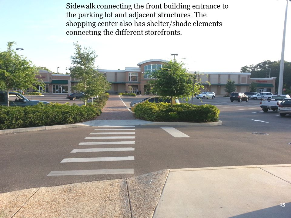 Sidewalk connecting the front building entrance to the parking lot and adjacent structures.