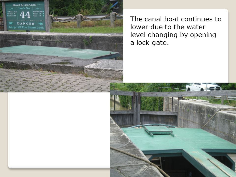 The canal boat continues to lower due to the water level changing by opening a lock gate.