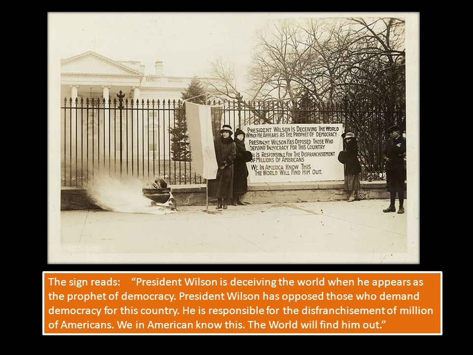 The sign reads: President Wilson is deceiving the world when he appears as the prophet of democracy.
