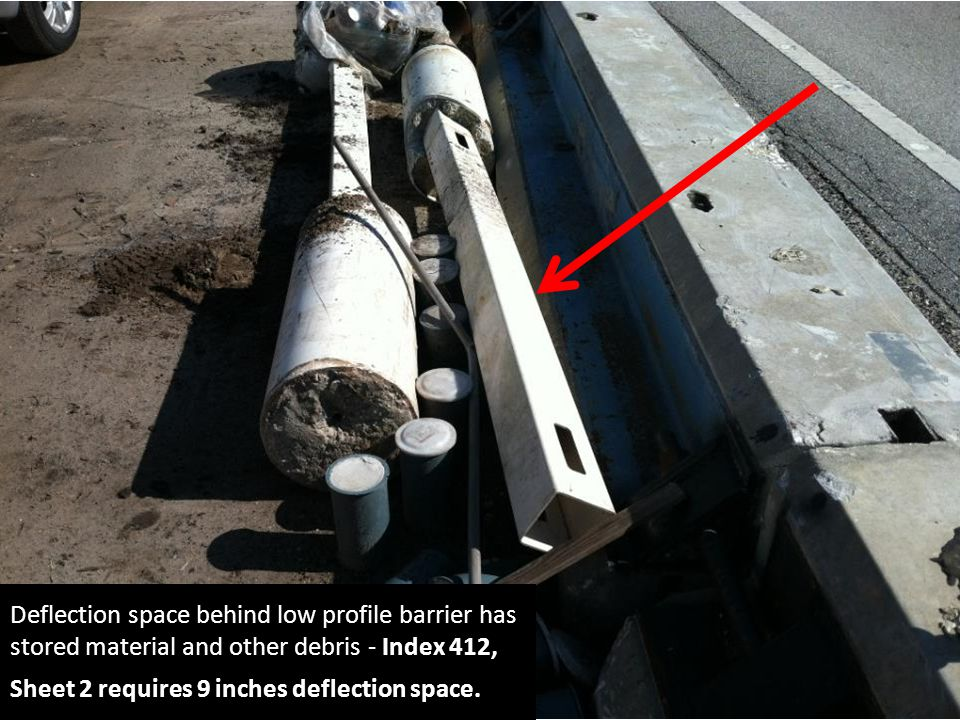Deflection space behind low profile barrier has stored material and other debris - Index 412, Sheet 2 requires 9 inches deflection space.