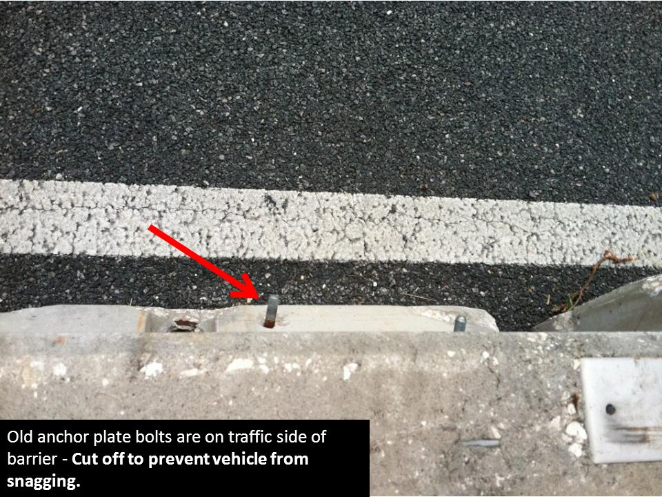 Old anchor plate bolts are on traffic side of barrier - Cut off to prevent vehicle from snagging.