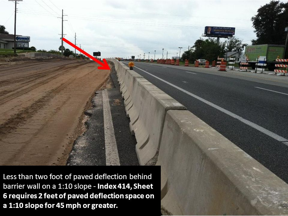 Less than two foot of paved deflection behind barrier wall on a 1:10 slope - Index 414, Sheet 6 requires 2 feet of paved deflection space on a 1:10 slope for 45 mph or greater.