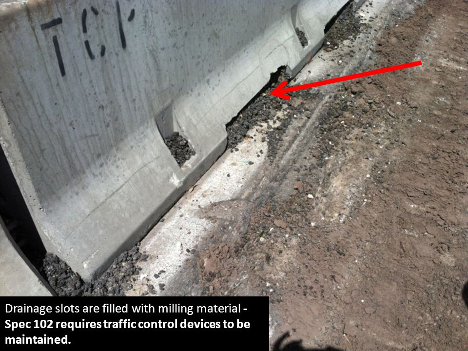 Drainage slots are filled with milling material - Spec 102 requires traffic control devices to be maintained.