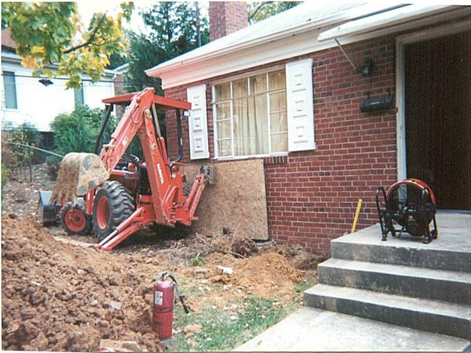 Is the backhoe supporting the house or the house supporting the backhoe