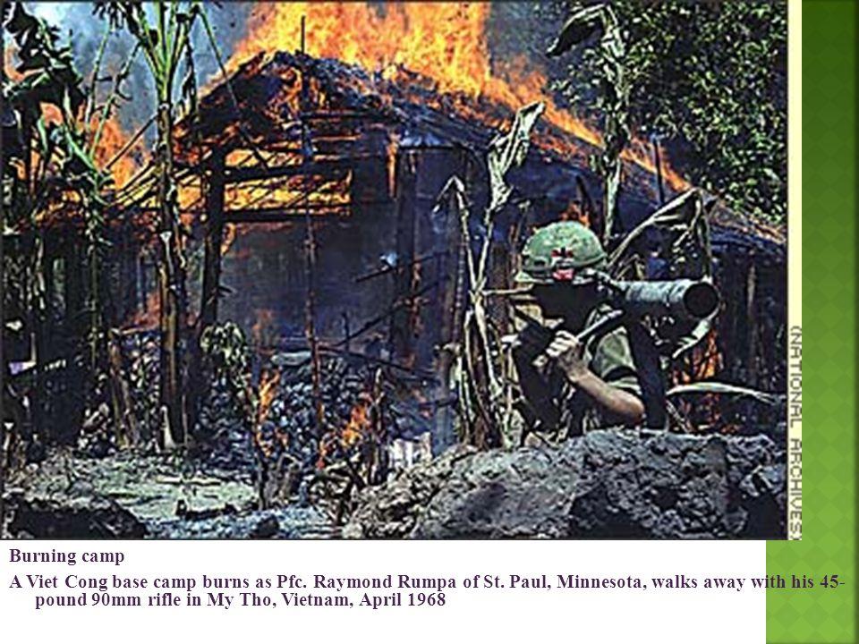 Burning camp A Viet Cong base camp burns as Pfc. Raymond Rumpa of St