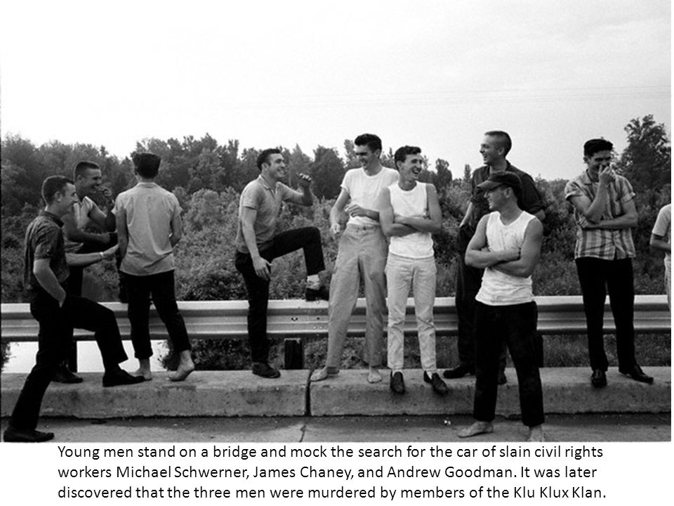 Young men stand on a bridge and mock the search for the car of slain civil rights workers Michael Schwerner, James Chaney, and Andrew Goodman.