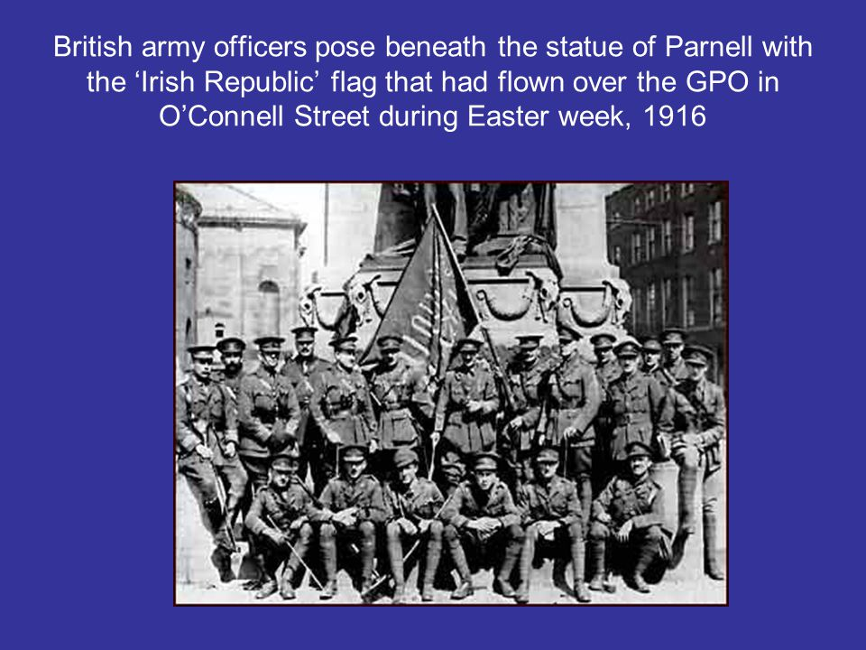 British army officers pose beneath the statue of Parnell with the 'Irish Republic' flag that had flown over the GPO in O'Connell Street during Easter week, 1916