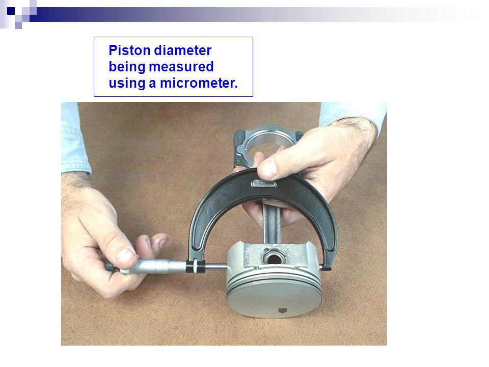 Piston diameter being measured using a micrometer.