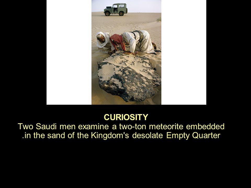 CURIOSITY Two Saudi men examine a two-ton meteorite embedded in the sand of the Kingdom s desolate Empty Quarter.