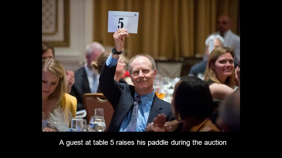 A guest at table 5 raises his paddle during the auction