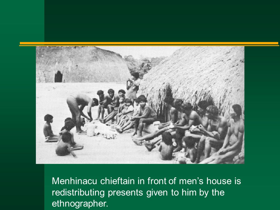 Menhinacu chieftain in front of men's house is redistributing presents given to him by the ethnographer.