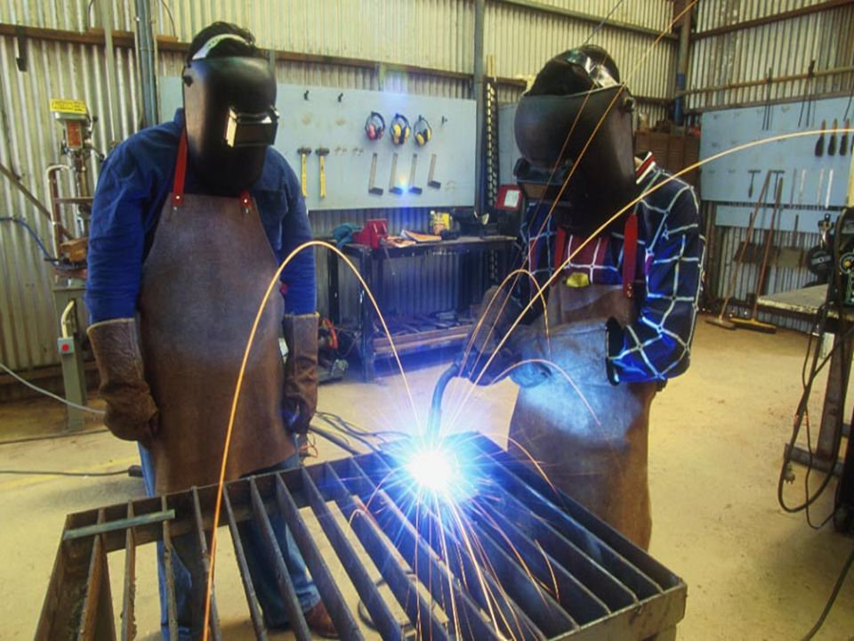 Workers performing arc welding operations with proper PPE.