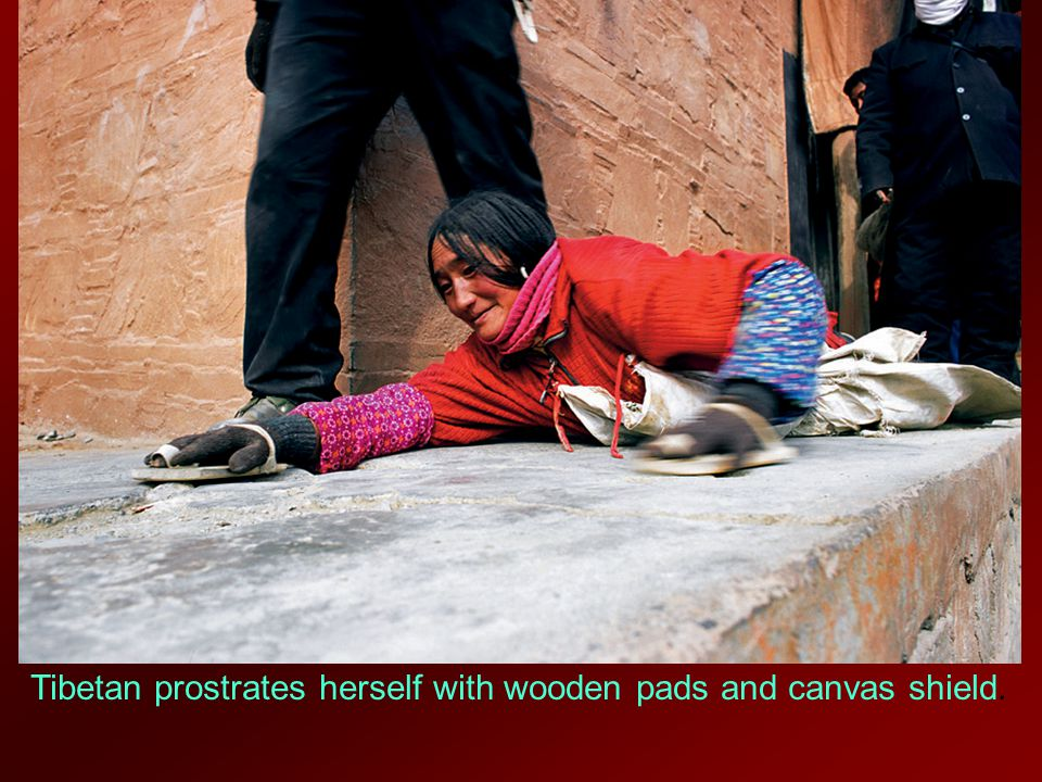Tibetan prostrates herself with wooden pads and canvas shield.
