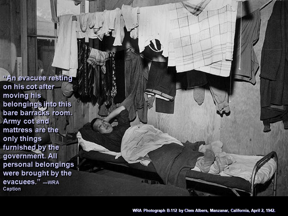 An evacuee resting on his cot after moving his belongings into this bare barracks room. Army cot and mattress are the only things furnished by the government. All personal belongings were brought by the evacuees. —WRA Caption