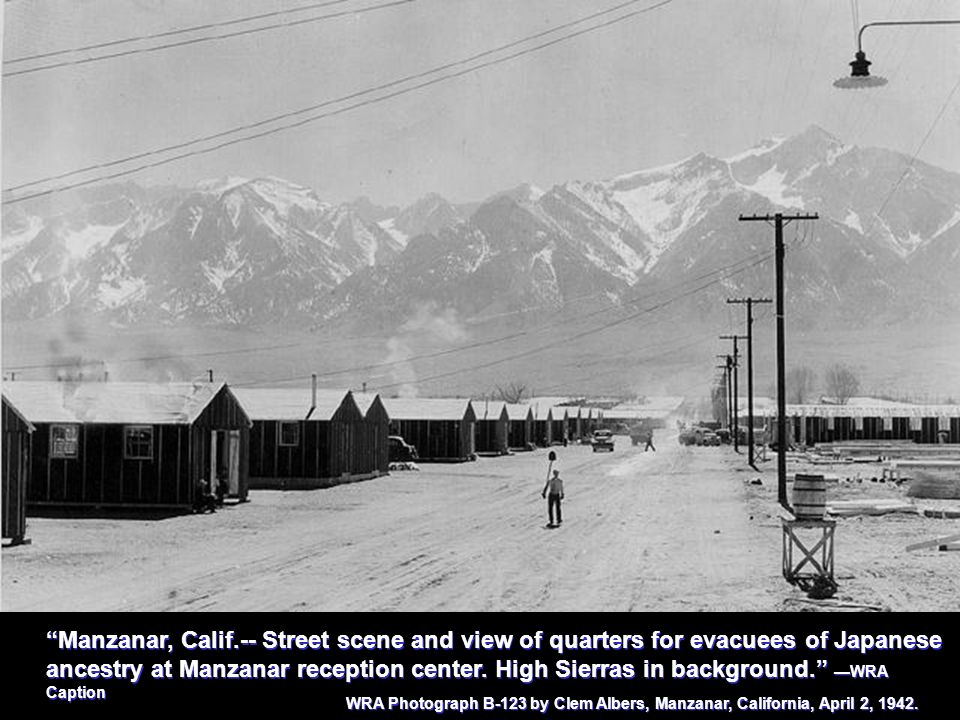 Manzanar, Calif.-- Street scene and view of quarters for evacuees of Japanese ancestry at Manzanar reception center. High Sierras in background. —WRA Caption
