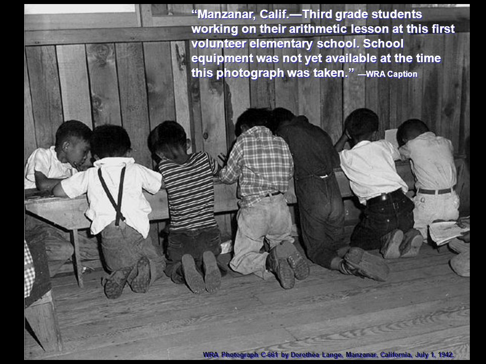 Manzanar, Calif.—Third grade students working on their arithmetic lesson at this first volunteer elementary school. School equipment was not yet available at the time this photograph was taken. —WRA Caption