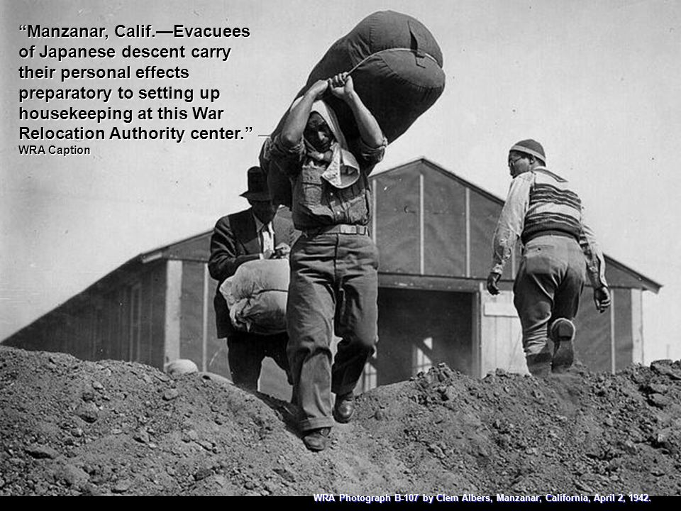 Manzanar, Calif.—Evacuees of Japanese descent carry their personal effects preparatory to setting up housekeeping at this War Relocation Authority center. — WRA Caption