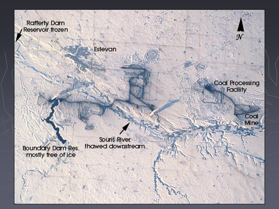 Snow and ice serve to accent human activities in this photograph taken by the Space Shuttle mission STS-98 crewmembers on February 17, 2001 (STS B-84). The Souris River stretches across the photograph from left to right, with the upstream Rafferty Dam Reservoir frozen over on the far left. Two power plants, the Boundary Dam Power Station and the Shand Power Station, can be identified by the smoke plumes and shadows of those plumes. The river is frozen over upstream of the Boundary Dam Power Station, but thermal loading from the plants has warmed the water in the Boundary Dam Reservoir so that it remains nearly ice free. Downstream of the reservoirs, thermal loading is sufficient to maintain open flow in the Souris River.