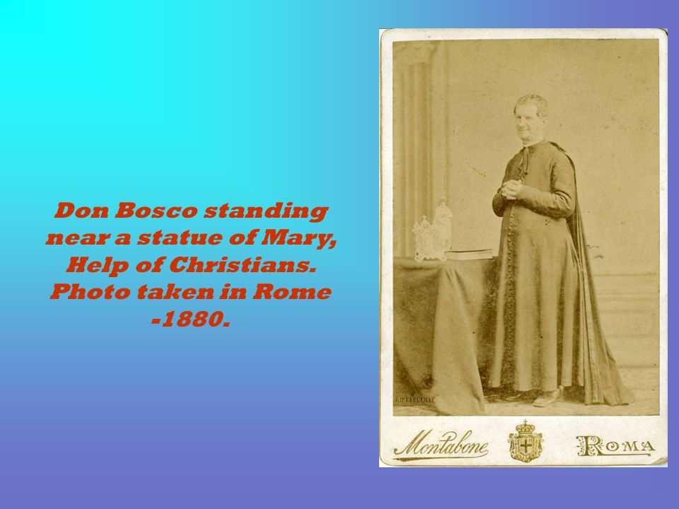 Don Bosco standing near a statue of Mary, Help of Christians