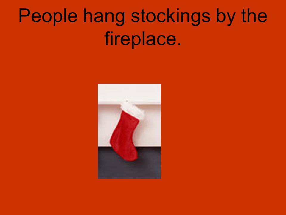 People hang stockings by the fireplace.