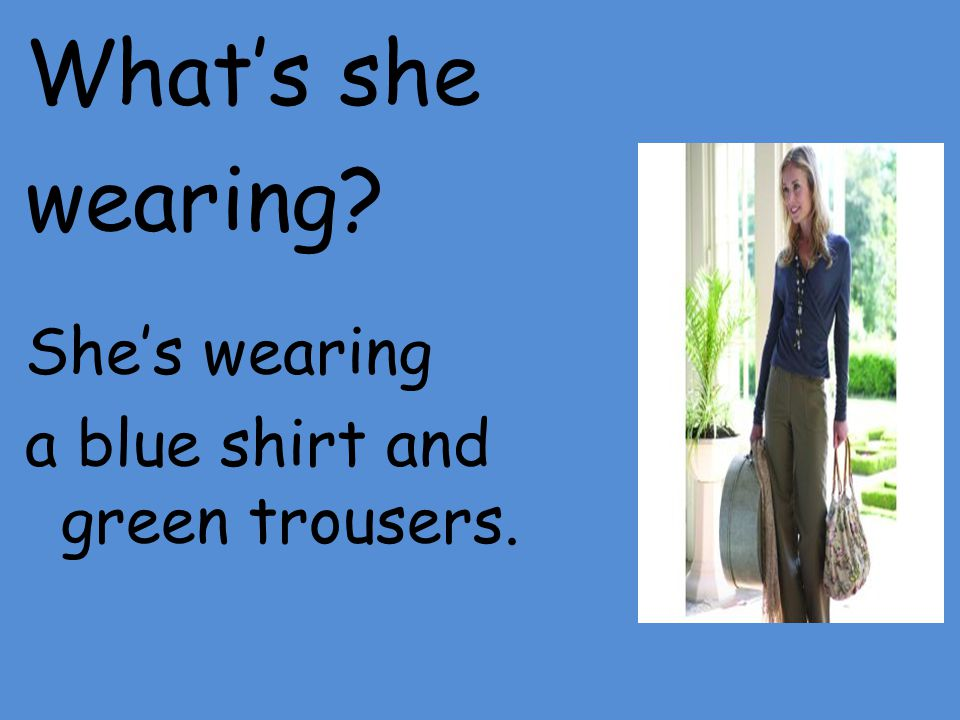 What's she wearing She's wearing a blue shirt and green trousers.