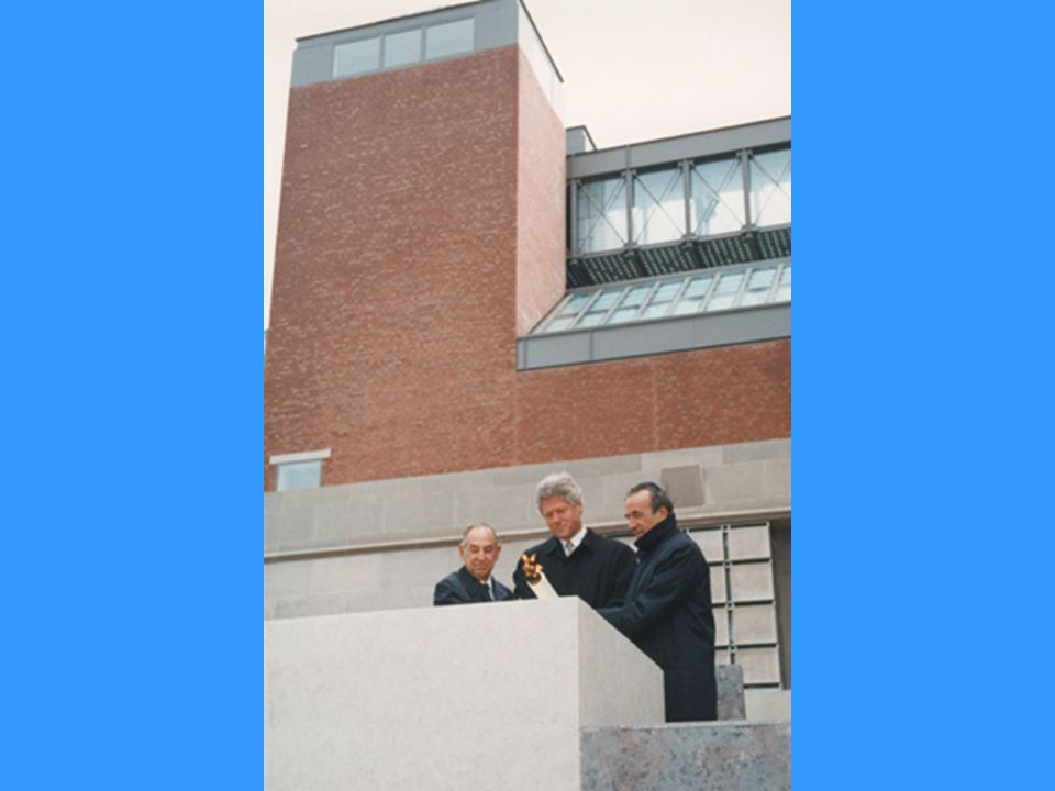 President Bill Clinton (center), Elie Wiesel (right) and Harvey Meyerhoff (left) light the eternal flame outside on the Eisenhower Plaza during the dedication ceremony of the U.S. Holocaust Museum.