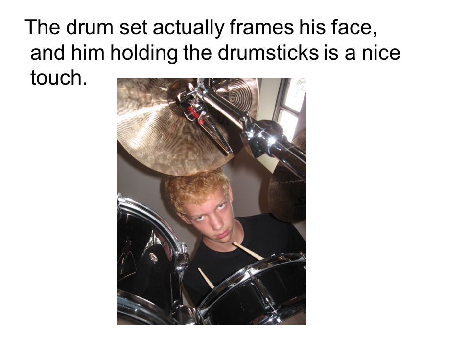The drum set actually frames his face, and him holding the drumsticks is a nice touch.