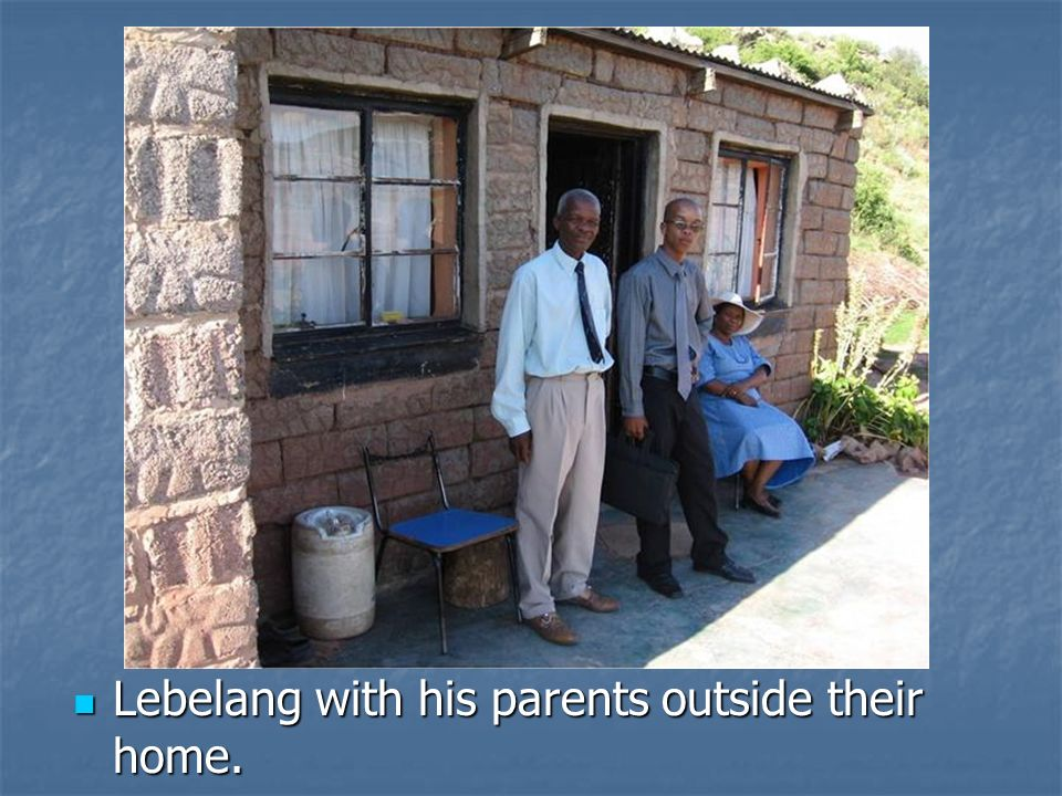 Lebelang with his parents outside their home.