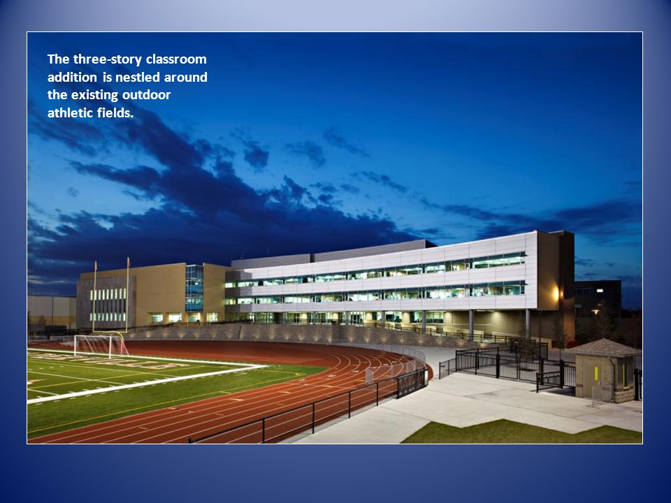 The three-story classroom addition is nestled around the existing outdoor athletic fields.
