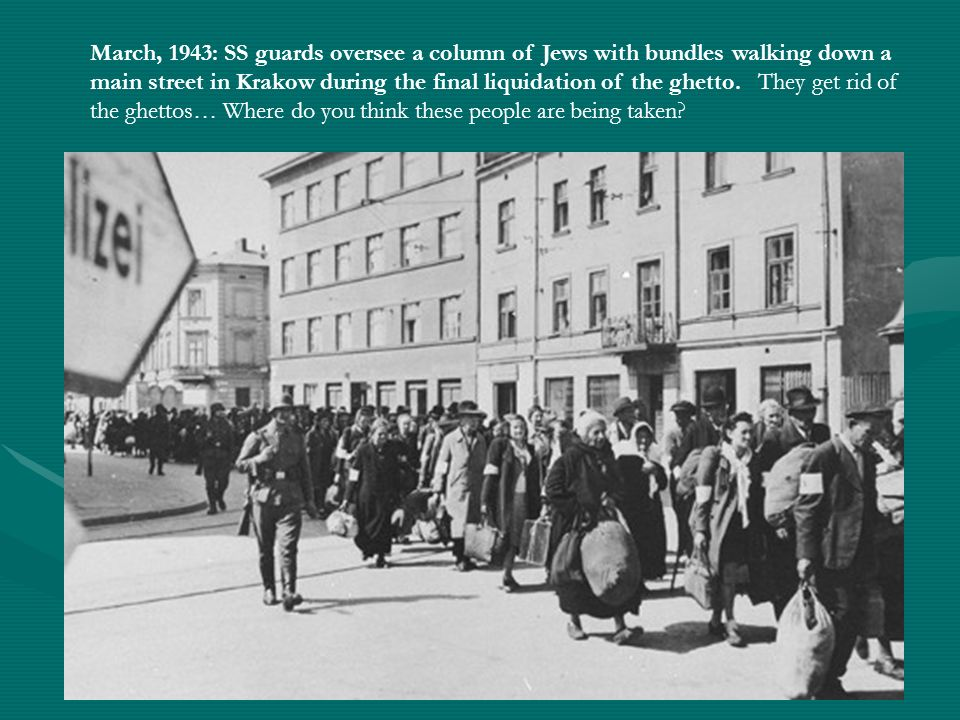 March, 1943: SS guards oversee a column of Jews with bundles walking down a main street in Krakow during the final liquidation of the ghetto.