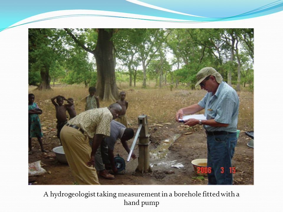 A hydrogeologist taking measurement in a borehole fitted with a hand pump