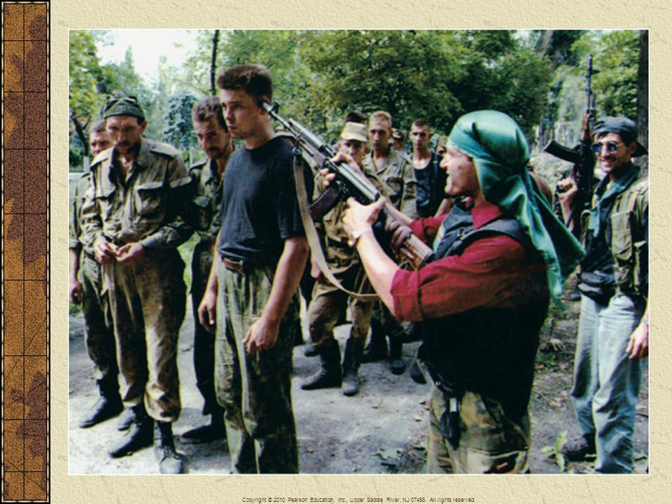 A Chechen fighter points his rifle at the head of a Russian prisoner of war outside the Chechen capital Grozny in August 1996.