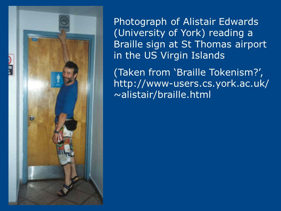 Photograph of Alistair Edwards (University of York) reading a Braille sign at St Thomas airport in the US Virgin Islands