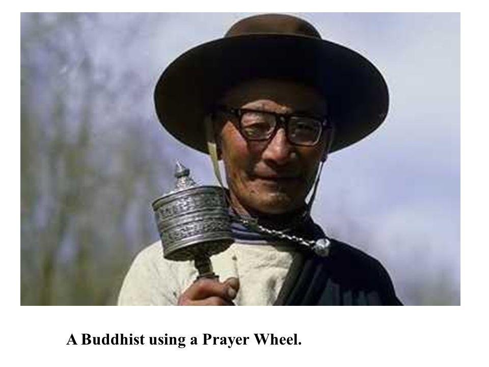 A Buddhist using a Prayer Wheel.