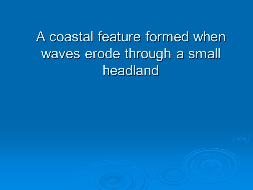 A coastal feature formed when waves erode through a small headland