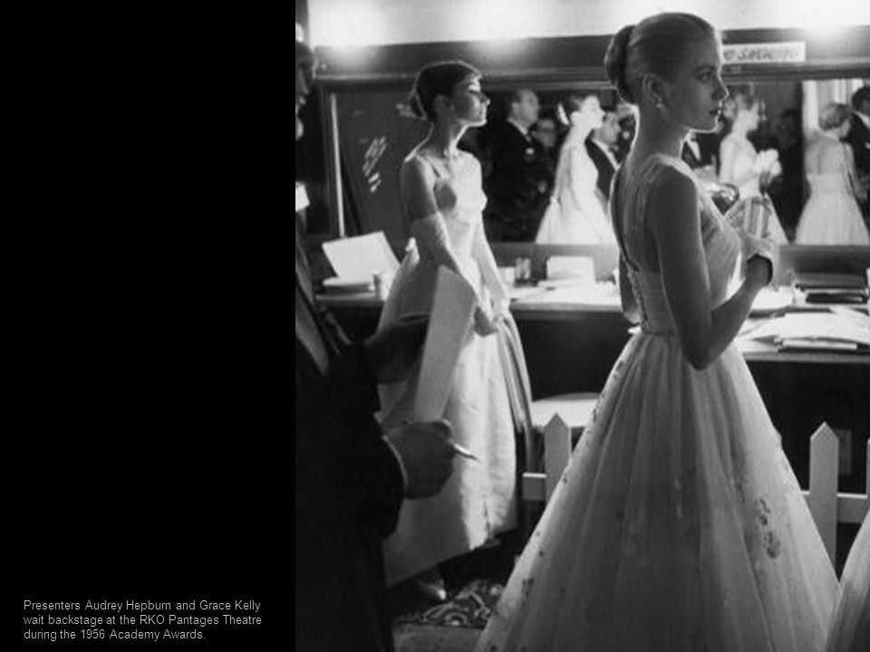 Presenters Audrey Hepburn and Grace Kelly wait backstage at the RKO Pantages Theatre during the 1956 Academy Awards.