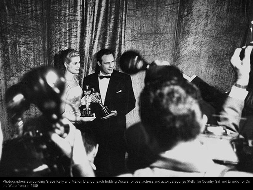 Photographers surrounding Grace Kelly and Marlon Brando, each holding Oscars for best actress and actor categories (Kelly for Country Girl and Brando for On the Waterfront) in 1955