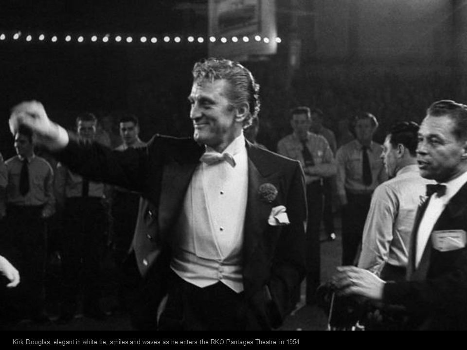 Kirk Douglas, elegant in white tie, smiles and waves as he enters the RKO Pantages Theatre in 1954