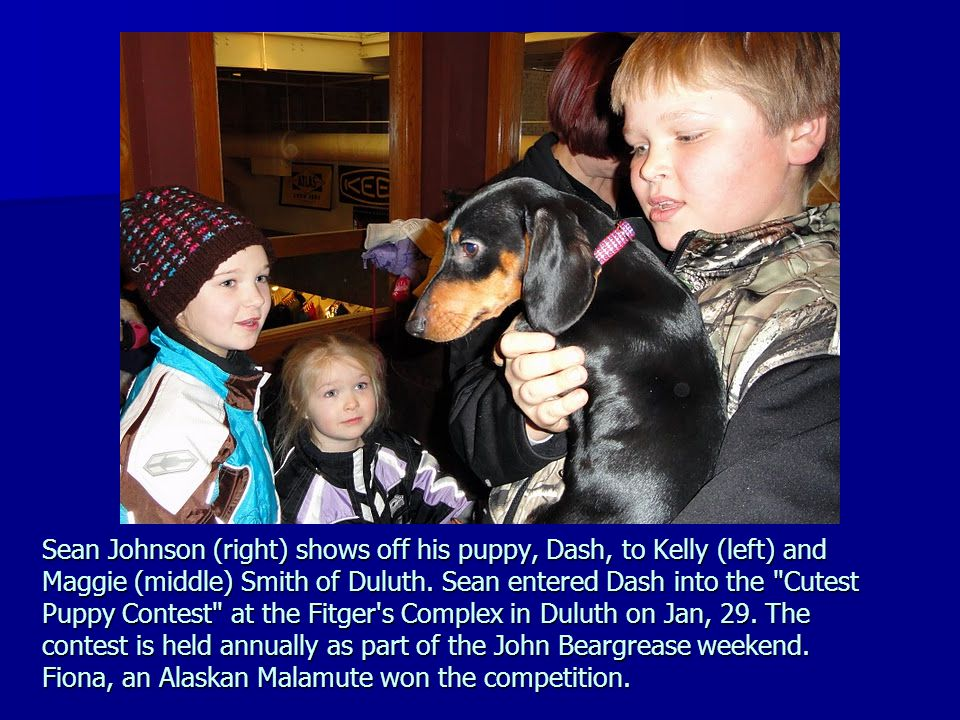 Sean Johnson (right) shows off his puppy, Dash, to Kelly (left) and Maggie (middle) Smith of Duluth.