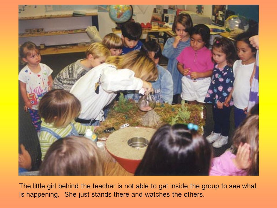 The little girl behind the teacher is not able to get inside the group to see what