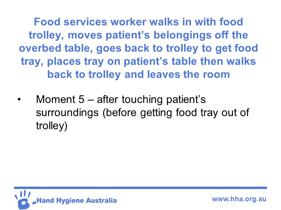Food services worker walks in with food trolley, moves patient's belongings off the overbed table, goes back to trolley to get food tray, places tray on patient's table then walks back to trolley and leaves the room